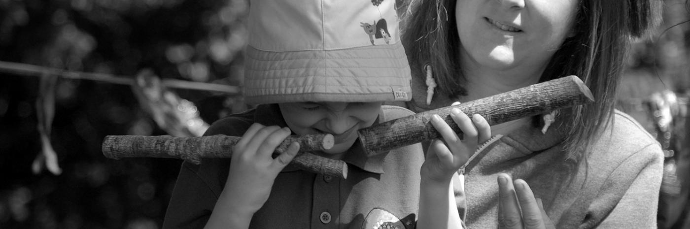 A boy holding some sticks